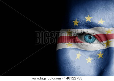 A young female with the flag of Cabo Verde painted on her face on her way to a sporting event to show her support.