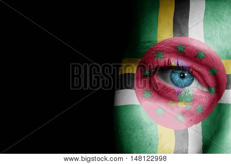 A young female with the flag of Dominica painted on her face on her way to a sporting event to show her support.