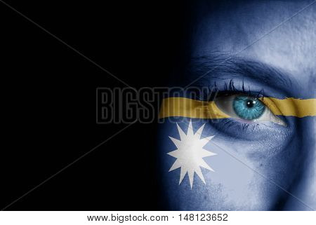 A young female with the flag of Nauru painted on her face on her way to a sporting event to show her support.