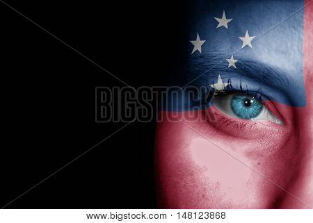 A young female with the flag of Samoa painted on her face on her way to a sporting event to show her support.