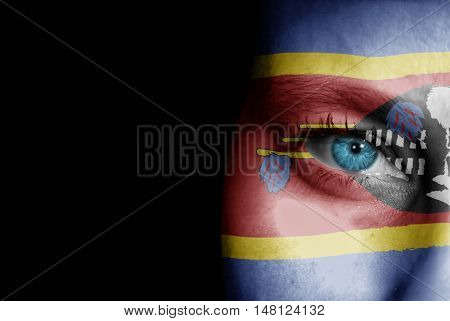 A young female with the flag of Swaziland painted on her face on her way to a sporting event to show her support.