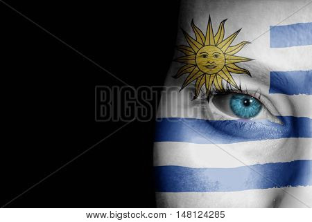 A young female with the flag of Uruguay painted on her face on her way to a sporting event to show her support.