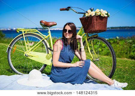 Happy Woman Sitting On The Grass With Vintage Bicycle On The Sea Coast