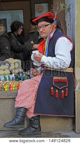 Krakow, Poland - October 29, 2015: man in national clothes is sitting outdoor in Krakow, Poland