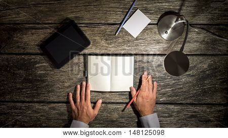 Top view of male hands about to make notes in blank notebook and tablet pen and paper placed around it on wooden study desk with table lamp turned on.