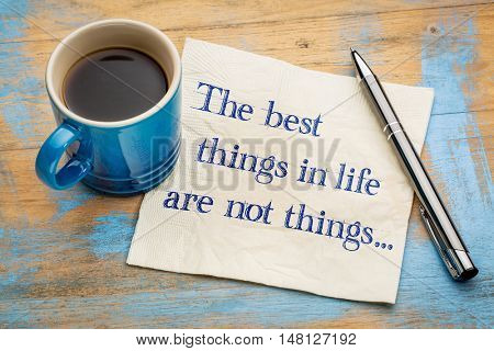 The best things in life are not things - handwriting on a napkin with a cup of espresso coffee