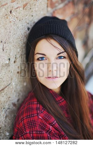 Portrait of a beautiful teen girl with blue eyes wearing a red shirt and a hat on a background of a brick wall