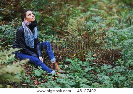 Beautiful brown-eyed brunette girl in a warm scarf jacket and jeans resting in autumn forest sitting on the ground among the withering grass