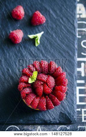 Tartlets with custard, fresh raspberries, served on dark table