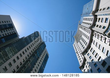 Two high-rise buildings in sunlight rays, reflections