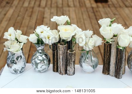 Beautiful decor at the wedding. Flowers standing on the table. Glass vases handmade glued a silver foil.