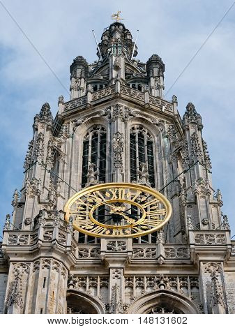 Detail of the facade of the Antwerp cathedral showing the golden clock on the tower near the Great Square Grote Markt in Antwerp, Belgium