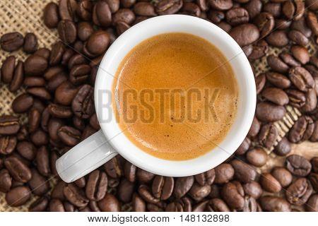fresh espresso with a beautiful crema and strewn mediumly roasted coffee beans on burlap
