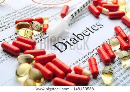 Pills and syringe on paper with text. Diabetes concept