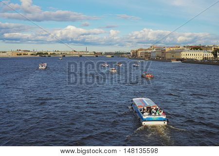 SAINT-PETERSBURG RUSSIA - SEPTEMBER 2016. Excursion boats with tourists sailing down the Neva and canals of St. Petersburg