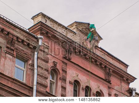 builder-climber hanging on the top of the facade of a building talking on a cell phone.