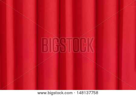 Bright red fabric, draped vertical folds of the curtain.