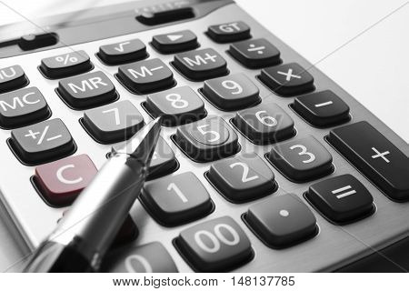 close up silver calculator with pen on white paper