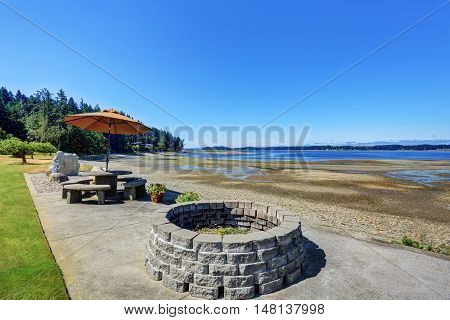 Back Yard With Stone Patio Table Set And Water View