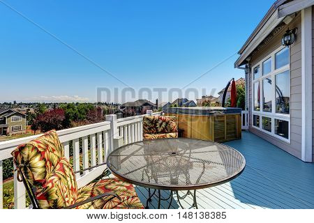 Wooden Walkout Deck With Outdoor Settees And Hot Tub