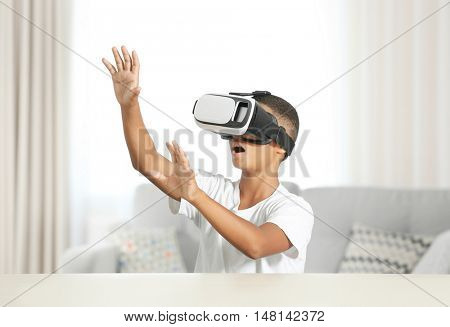 African-American boy wearing virtual reality glasses and sitting at a table