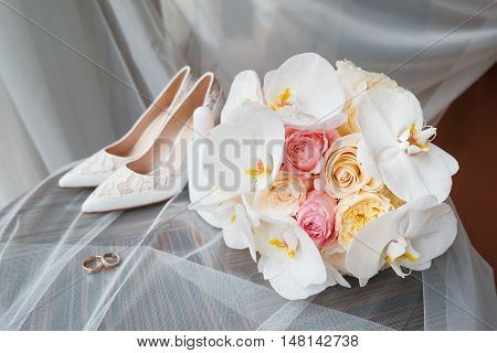 Bride's accessories - bouquet wedding rings and shoes. Floral composition with roses and orchids.