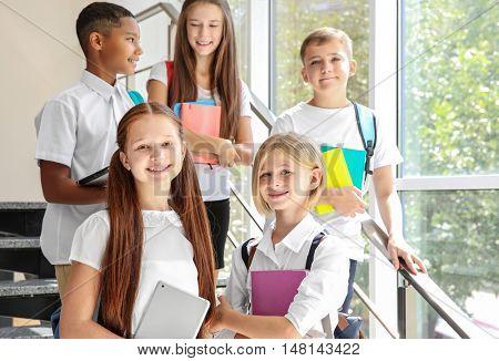 Schoolchildren standing on stair-steps near window at school