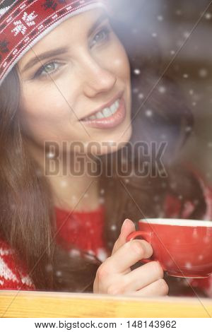 woman drinking coffee and looking out of the window on winter day.