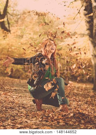 Autumn people nature concept. Female is playing with leaves. Girl is spending spare time outside.