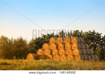 Stack of bales of hay at sunset. End of summer season concept.