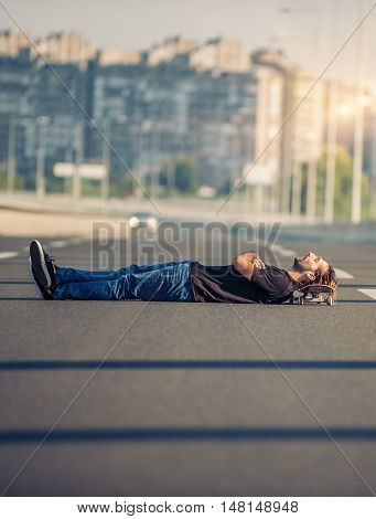 Crazy Skateboarder Lying Down At The Middle Of A Highway Bridge With His Head On The Skate Board