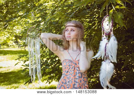 Portrait of Boho Young Girl with Dreamctahcer Hanging Alongside Outdoor