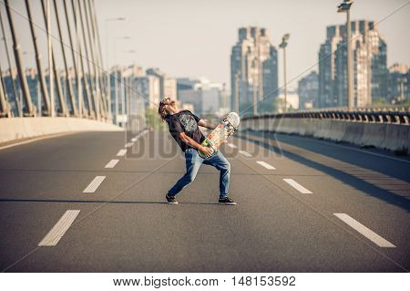 Happy Skateboarder On The Bridge Playing Guitar On His Skate Board