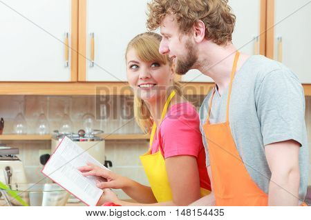 Happy young couple having fun in modern kitchen at home preparing fresh vegetables food reading cookbook looking for recipes