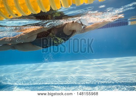 Powerful female swimmer swims underwater in the swimming pool outdoors. She wears a black-gray swimsuit with patterns, a white swim cap and swim glasses. Sunlight falls from above. Horizontal.