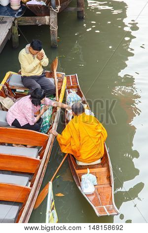 Ratchaburi Thailand - March 20 2016 : Buddhist monk on boat in morning at Damnoen Saduak Floating Market tourists visiting by boat located in Ratchaburi Thailand.