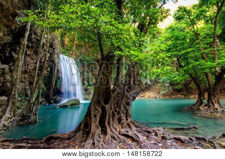Jungle landscape with flowing turquoise water of Erawan cascade waterfall at deep tropical rain forest. National Park Kanchanaburi Thailand