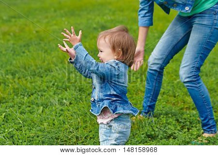 mother walking with a baby on the grass