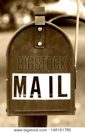 Old vintage black mailbox on front lawn with flag up