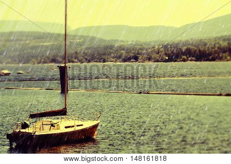 In the midst of a rainy storm, with a lovely landscape of trees and mountains in behind sits a lonely sailboat anchored in the middle of a stormy lake. As the rain falls the yellow hue of the sky shines down upon the water.