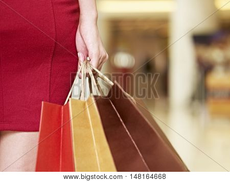 young woman walking with shopping bags in mall close-up on hand
