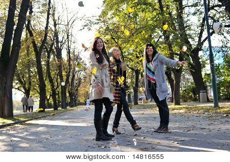 Happy three friends having fun outdoors in nature