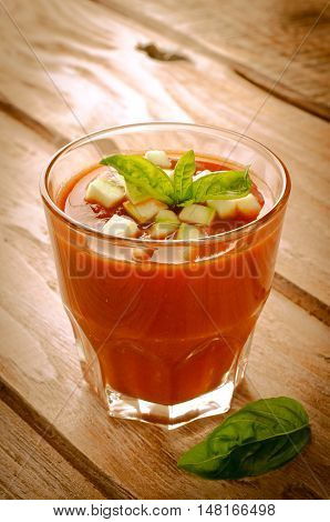 Tomato gazpacho in a glass with basil ang zucchini, on wooden background, toned
