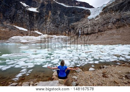 Woman sitting in yoga pose by lake. Angel Glacier at Mount Edith Cavell. Jasper National Park. Canadian Rockies. Alberta. Canada.