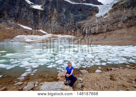 Woman smiling by moraine lake with icebergs. Angel Glacier at Mount Edith Cavell. Jasper National Park. Canadian Rockies. Alberta. Canada.