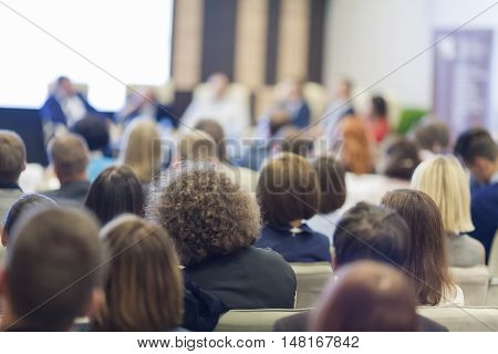Business Concepts. People At the Conference Listening to Hosts Speakers Sitting In Front On Stage Before The Audience.Horizontal Image