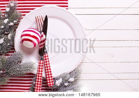 Holiday table setting. White plate knife and fork napkin and christmas ball in white and red colors on white wooden table. Top view. Selective focus is on cutlery.Place for text.