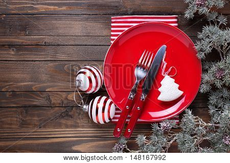 Red plate knife and fork napkin and christmas decorations in white and red colors on dark wooden table. Christmas table setting.Top view. Place for text. Selective focus.