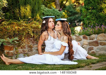 Two cute sisters fooling around with books sitting on the lawn. Girls put books on his head and are posing funny face.