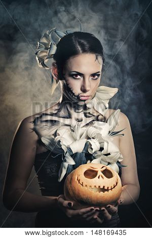 Young attractive girl with creative make-up for Halloween. Portrait close-up pumpkins. Mysterious and frightening image of lilies and red eyes. Witchcraft. Dreadful. Jack-o'-lantern